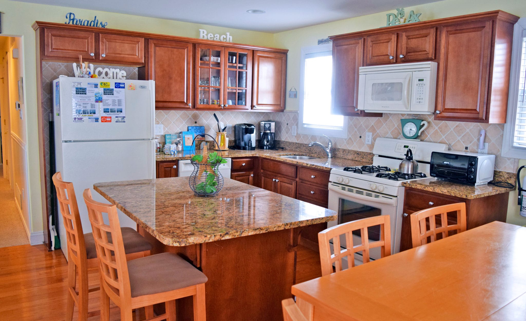 Spacious kitchen features island, granite countertops, and full kitchenware and appliances - Ocean City, New Jersey Family Vacation Rental